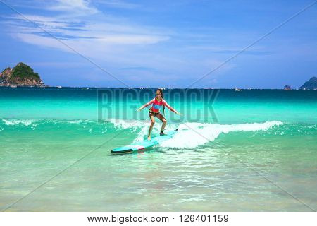 Kid girl is learning surfing, riding a wave