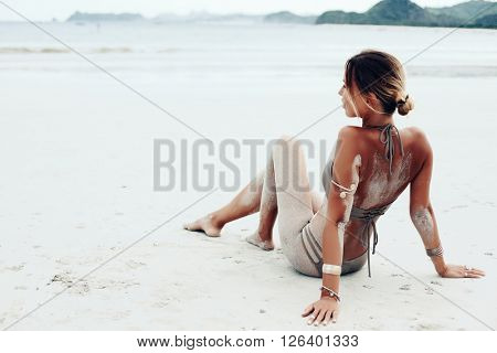 Beautiful bohemian styled and tanned girl at the beach