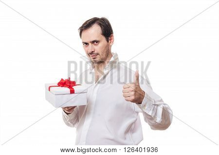 The man with a bristle in a white shirt holds a gift in hand shows a class