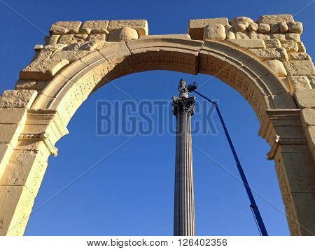 LONDON UK - APRIL 19 2016: View through a recreation of the historic Arch of Triumph from the ancient Syrian city of Palmyra looking towards Nelson's Column in London's Trafalgar Square. The arch has been reconstructed using 3D printing. The column is bei