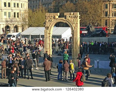 LONDON UK - APRIL 19 2016: Crowds in London's Trafalgar Square surrounding a recreation of the historic Arch of Triumph from the Syrian city of Palmyra. The ruin has been recreated using 3D printed marble and will travel the world.