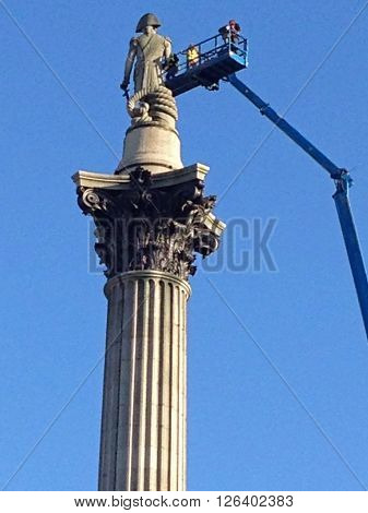 LONDON UK - APRIL 19 2016: Engineers using a tall cherry picker inspect the statue of Lord Nelson on top of the tall column in Trafalgar Square London. The day before the landmark had been scaled by Greenpeace activists who placed a mask on the statue.