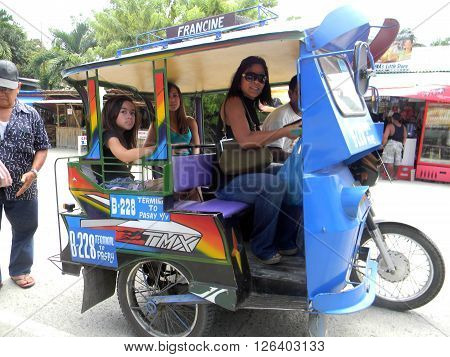 MAASIN, SOUTHERN LEYTE / PHILIPPINES - AUGUST 3, 2011: Passengers ride a motorcycle taxi through the island of Southern Leyte.