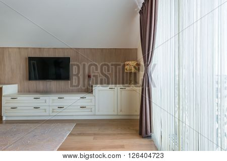 White wooden commode with tv unit near big window