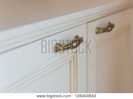 Golden furniture handle on white wooden dresser or night table