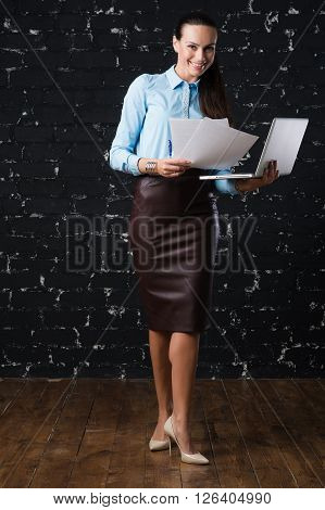 Russian business lady looking to the camera and smiling on the black brick background for use e.g. in collages, presentation