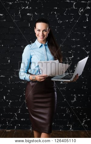 Russian business lady looking straight to the camera on the black brick background for use e.g. in collages, presentation