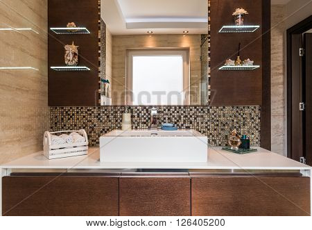 Closeup of washbasin in bathroom interior in earth tones