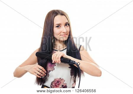 The beautiful woman corrects hair curling tongs and smiles.