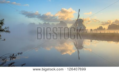 Reflection Of White Wooden Windmill In River