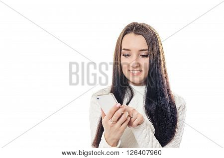 The woman in a white sweater goes through pages on sensor phone and smiles