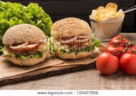 Two homemade vegetarian burgers with fresh organic vegetables on rustic wooden background