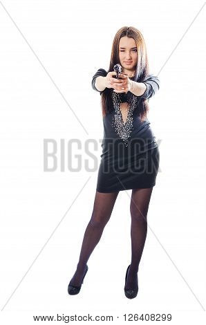 The young woman in a dress aims from the pistol