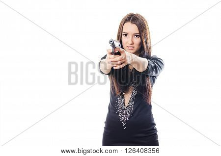 The dangerous young woman with long hair shoots from the pistol having slightly opened a mouth