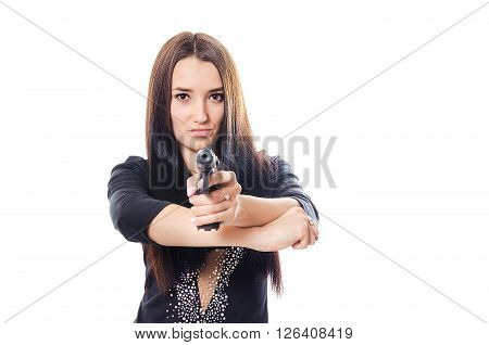 The dangerous young woman in a dress aims from the pistol