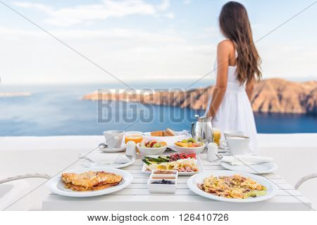 Breakfast table and luxury travel woman on santorini. Well balanced perfect breakfast table served at resort. Female tourist is looking at beautiful view of sea and caldera enjoying her vacation.