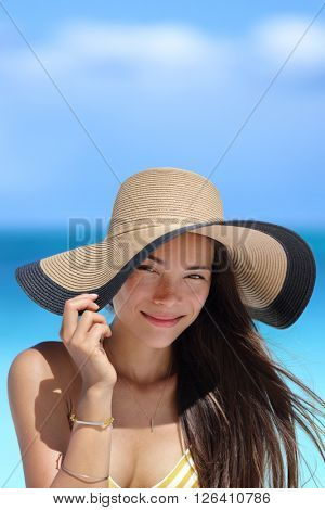 Portrait of Asian woman with beach hat smiling happy wearing fashion straw hat for skin care sun protection. Face skincare beauty. Beautiful mixed race young adult girl on summer vacation travel.