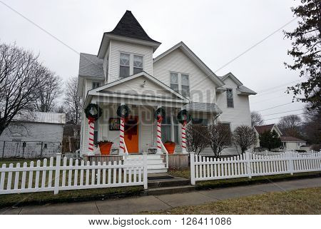 HARBOR SPRINGS, MICHIGAN / UNITED STATES - DECEMBER 23, 2015: A white home with picket fence and a front porch, decorated festively for the Christmas Holiday, on Traverse Street in Harbor Springs.