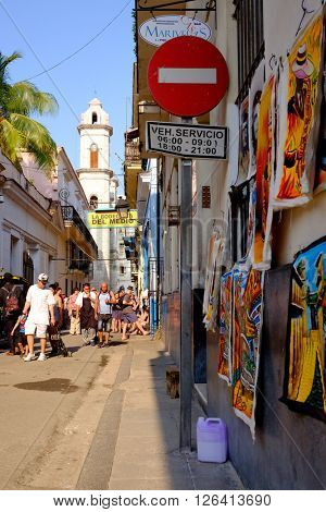 HAVANA,CUBA- MARCH 15,2016 : Colorful street scene next to the famous Bodeguita del Medio and the Cathedral Church in Old Havana