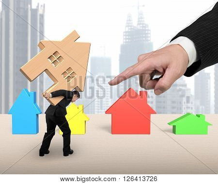 Businessman Carrying Wooden House With Big Forefinger Pointing At