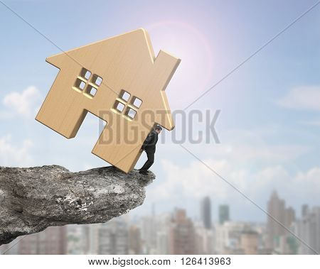 Man holding wooden house on cliff edge on sunny sky cityscape background.