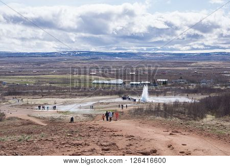 Strokkur Geysir erupting while tourists look on, high view point ** Note: Soft Focus at 100%, best at smaller sizes