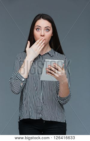 Amazed businesswoman holding tablet computer and looking at camera over gray background