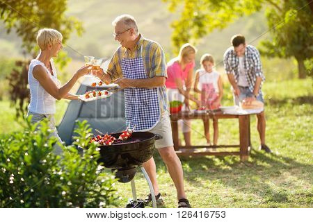 smiling grandparents drinking wine at barbecue