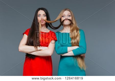 Two funny girls making mustache with their hair over gray background