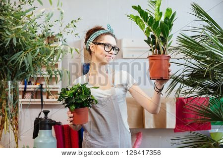 Pensive cute young woman florist in glasses holding plants in flowerpots and thinking
