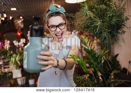Playful attractive young woman florist pointing with water sprayer on you in flower shop