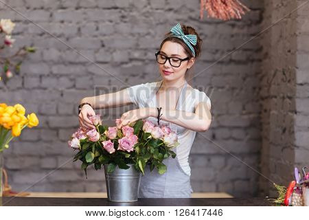 Beautiful young woman florist standing and arranging roses in bucket in flower shop