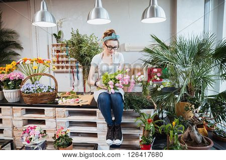 Cute lovely young woman florist sitting and arranging pink tulips in flower shop
