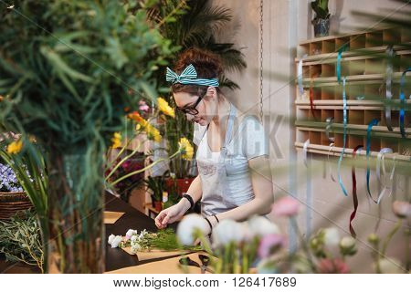 Beautiful young woman florist in apron and glasses making bouquet and working in flower shop