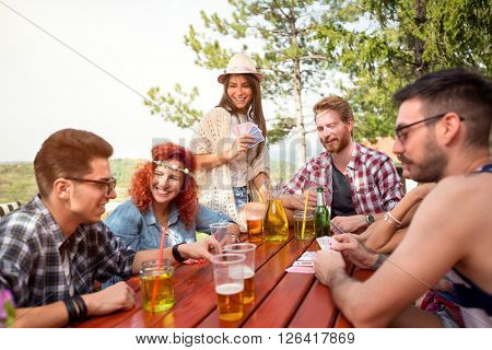 Youth enjoying in leisure with friends, cards game and cold drink in forest