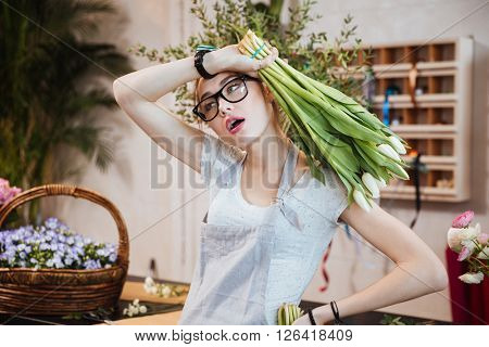Exhausted pretty young woman florist holding bunch of white tulips and working in flower shop