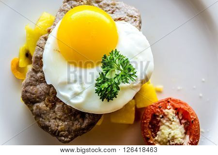 Sirloin Steak Topped With Fried Egg And Breakfast Potatoes