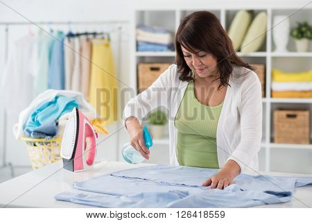 Asian housewife spraying  shirt nicely before ironing