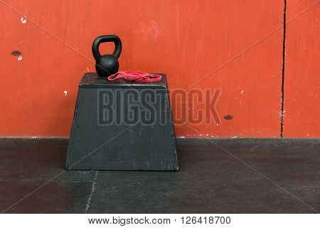 Black kettle bell and red fitness band on a black jump box, against a red wall