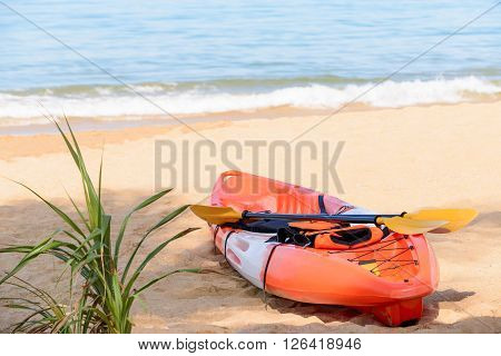 A canoe on the beach with paddles and life jacket at sunny day.