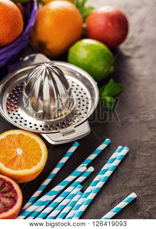 Juicer with different citrus fruits oranges limes and lemons. On the stone table.