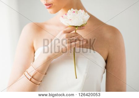 glamour, beauty, jewelry and luxury concept - close up of beautiful woman with golden ring and bracelet holding flower