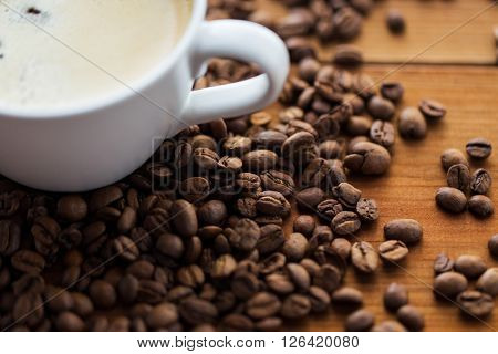 caffeine, objects and drinks concept - close up coffee cup and beans on wooden table