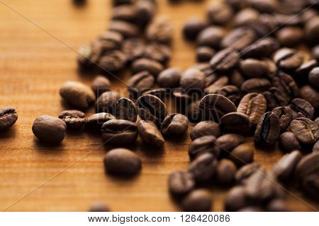 raw and agriculture concept - close up coffee beans on wooden table