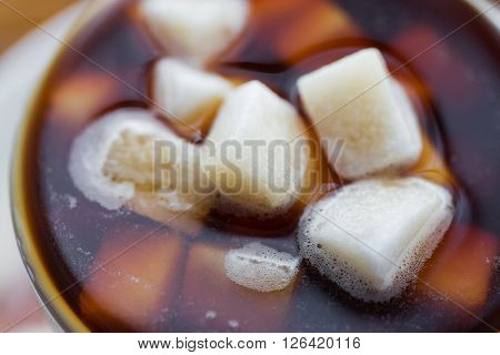 unhealthy eating, object and drinks concept - close up of lump sugar heap drowned in cup of coffee or tea