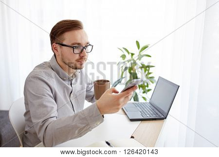 business, technology, startup and people concept - businessman or creative male worker texting on smarphone and drinking coffee at home office