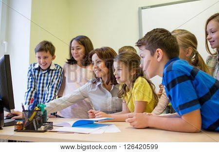 education, elementary school, learning, technology and people concept - group of school kids with teacher looking to computer monitor in classroom