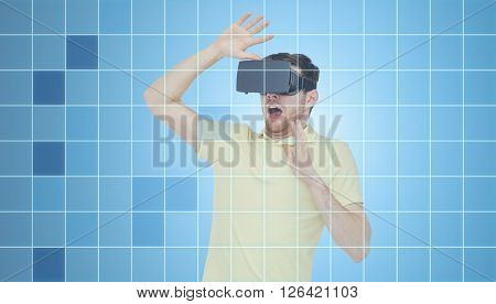 3d technology, virtual reality, entertainment and people concept - scared young man with virtual reality headset or 3d glasses playing game over blue grid background