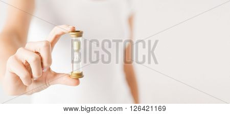 deadline, time management concept - close up of woman hand holding hourglass.