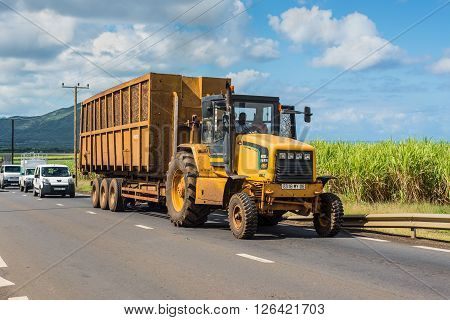 Cascavelle Mauritius - December 10 2015: Truck with full load of harvested sugarcane in the countryside near Cascavelle Mauritius. Agricultural landscape of Mauritius.